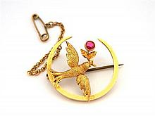 An Australian 15ct Yellow Gold Crescent Brooch with a Swallow and Flower with a Round Synthetic Ruby
