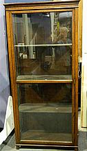 A freestanding oak display case with glazed door and four fixed shelves