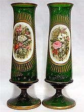 An antique pair of green glass mantle vases with centre enamels ceramic plaques of handpainted flowers with gilt decoration
