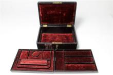 An antique leather and velvet jewellery box with two lift out compartment trays and key.