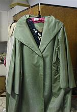 A green satin coat and black beaded top