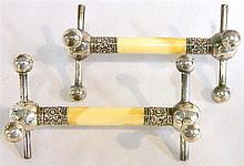 A pair of Sterling Silver and ivory knife rests