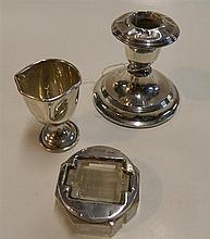 A sterling silver weighted candlestick, a sterling silver egg cup and a glass and sterling silver stamp roller