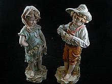 A charming pair of ceramic figures of a boy and girl with fruit and flowers.