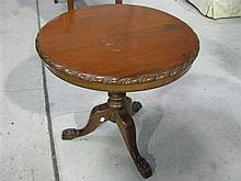 A round cedar side table with ball and claw feet.