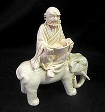 An Asian Porcelain Statue of an Elder on an Elephant