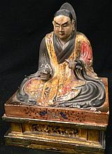 A Late meiji period wood carving of a monk on a pedestal