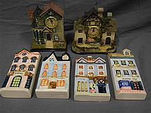 Four ceramic building form wall plaques and two cottage clocks