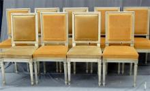 A set of nine dining chairs with a distressed ivory finish, upholstered seat and back