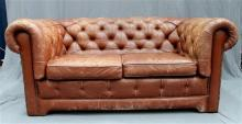 A distressed tan buttoned back chesterfield two-seater lounge