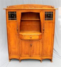 A maple 1920s arts and crafts book case with lead light inserts