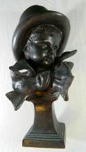 A bronze bust depicting a young boy wearing a top hat after Jean-Antoine Houdon