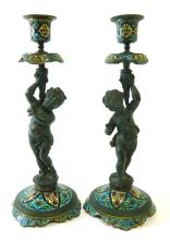 A pair of bronze and enamel putti candlesticks