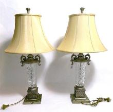 A pair of crystal lamp bases with silvered metal mounts and cream silk shades