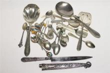 A collection of Silver-Plate Cutlery items, including a Brazilian Airways Inox sheathed Knife