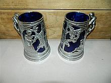 A pair of blue glass and silver plate decorative tankards