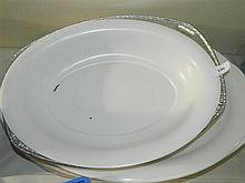 A large quantity of white plastic serving platters