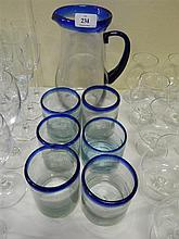 A hand blown glass jug and glasses with blue rim