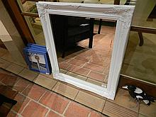 A bevel edged mirror in ornate white frame