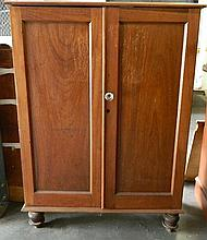 An Australian cedar two door fitted cabinet on later turned feet