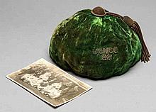 A green cricket cap circa 1920,  inscribed U.C.N.C.C., 1921; sold with