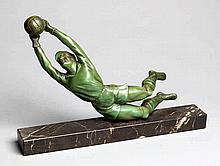 A spelter figure of a diving goalkeeper,  with green patina, set on a m