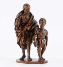 CONTINENTAL CARVED FIGURE OF A SCHOLAR AND CHILD