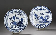 Paire d'assiettes en porcelaine blanche décorée en bleu cobalt sous couverte de branches de pivoines épanouies et bambous en réserve japonisante.