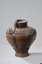 Récipient à poudre composée d'une jarre en grès porcelaineux à glaçure monochrome brune serti d'un piètement et d'une collerette en fer forgé ouvragé de rinceaux à l'épaulement terminée au col par un couvercle et un crochet de suspension .