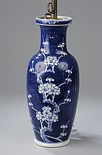 Vase balustre en porcelaine blanche décoré en réserve d'une branche de cerisier en fleurs sur fond bleu outremer à la base le double cercle en bleu sur fond blanc.