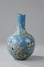 Vase à fond plat, panse globulaire et col cylindrique en porcelaine moulé en relief d'un décor de branches de prunus habitées de passereaux en polychromie sur fond monochrome bleu de poudre.