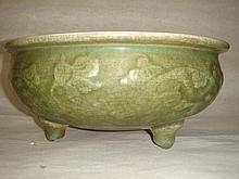 Brûle parfum Ding à large cavité circulaire et creuse en épaisse porcelaine ocre décorée en relief  de motifs floraux sous glaçure monochrome céladon finement craquelé.