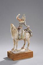 Cavalier Perse chevauchant sa monture les quatre jambes au sol, vêtu d'une tunique ceinturé et d'un bonnet, portant une barbe et faisant le geste de tenir son chien grimpé sur la croupe du cheval.