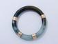 Bracelet jonc en jade, rehaussé de 4 anneaux en or.. Poids brut: 76.20 g. Diam: 6 cm.