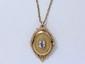 Broche pendentif en or, stylisant un médaillon centré d'une aigue marine en serti clos dans un décor ajouré, suspendu à une chaîne maille forçat agrémenté d'un fermoir anneau ressort.. Poids brut : 13.70 g. Long: 50 cm.