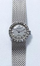 NIVADA. Montre bracelet de dame en or gris 18K, cadran argenté légèrement tâché avec index bâtons appliqués, lunette diamantée. Mouvement mécanique signé. Bracelet en or gris 18K, maillons tressés avec fermoir réglable à cliquet en or gris 18K. Vers