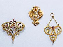 Lot en or composé d'une broche, d'un pendentif et d'une pince, chacune ajourée, agrémentée de pierres rouges ou de petites roses. Travail français, vers 1900.. Poids brut: 8.50 g l'ensemble.