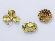 Lot en or composé d'une broche circulaire à bords dentelés et décor ciselé, d'une broche en forme de trèfle, chacune agrémentée d'une petite perle. On y joint un coulant en pomponne à décor de cartouche estampé et ciselé. Travail français de la fin