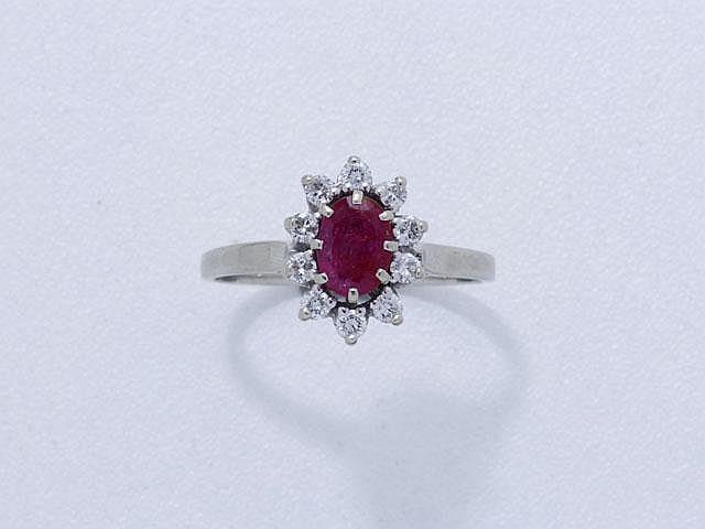 Bague en or gris, ornée d'un rubis ovale facetté en serti griffe dans un entourage de diamants brillantés. (égrisures). Poids brut: 3.50 g. TDD: 58.5.
