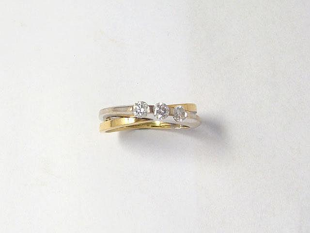 Bague 2 tons d'or, ornée de 3 diamants brillantés en serti griffe.. Poids brut: 4.80 g. TDD: 55.