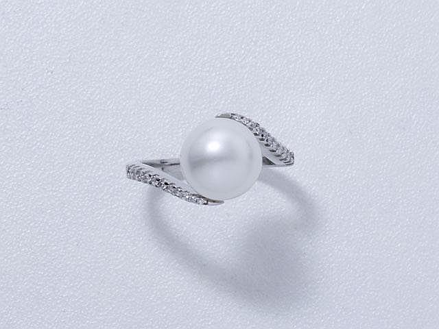 Bague en or gris, ornée d'une perle de culture d'eau douce épaulée de diamants brillantés.. Poids brut: 4.60 g. TDD: 52. (manque)