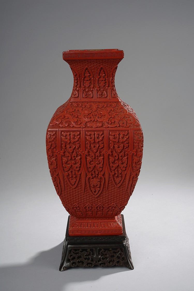 Vase de forme « Hu » quadrangulaire finement ciselé sur quatre registres horizontaux de frises d'écoinçons et de guirlandes fleuries, le col à décor de Leiwen et la base de fleurs de lotus. A la base marque Qianlong incisée dans une laque noire .