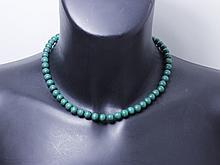 Collier composé d'un rang de perle de malachite d'environ 7.9 mm, agrémenté d'un fermoir à cliquet en or 18 K rehaussé d'une émeraude ronde facettée. (égrisures). Poids brut: 57.70 g. Long: 44 cm.