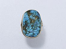Importante bague ovale en or 18 K, ornée d'une turquoise gravée dorée en serti clos. Travail français.. Poids brut: 10.50 g. TDD: 56.5.