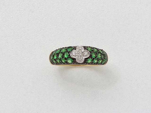 Bague jonc en or, ornée d'un pavage de grenats verts, centrée d'un motif cruciforme diamanté. (égrisures). Poids brut: 4.80 g. TDD: 53.