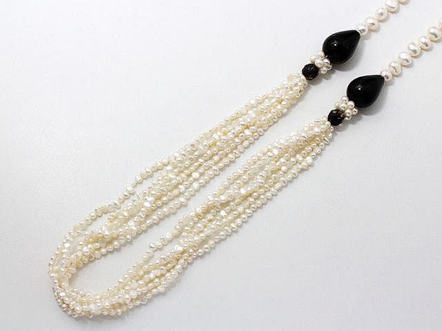 Collier composé de perles de culture d'eau douce rehaussées de 2 gouttes imitant l'onyx, agrémenté d'un fermoir en métal.. Long: 80 cm.