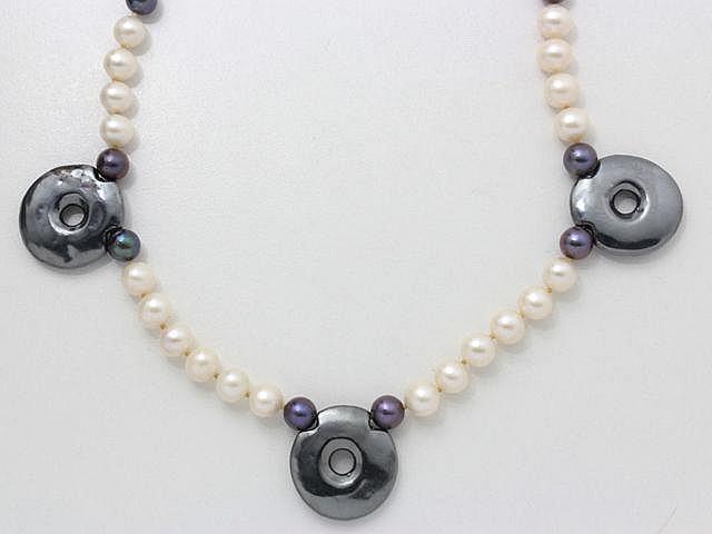 Sautoir composé d'un rang de perles de culture d'eau douce, rehaussé de 3 motifs fantaisies nacrés.. Long: 73 cm.