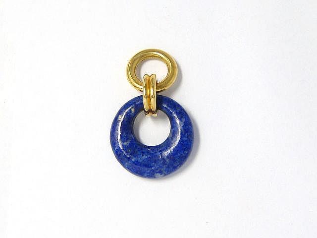 Pendentif composé d'un anneau ajouré en lapis lazuli, orné d'une bélière godronnée en or.. Poids brut: 7 g.