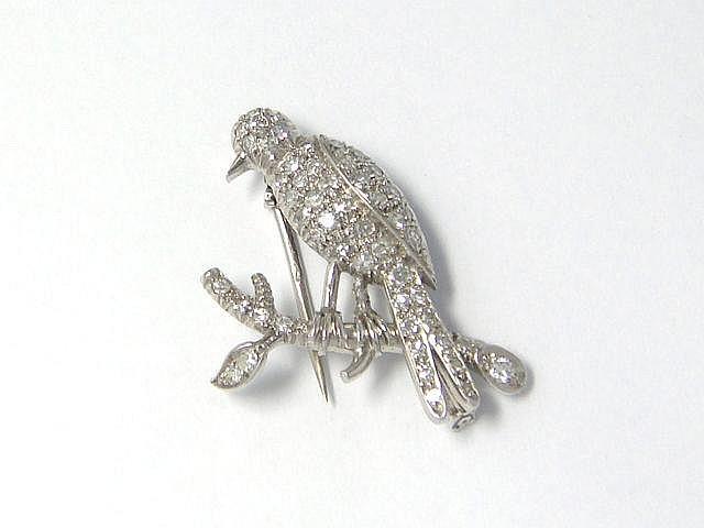Amusante broche clip en or et platine, stylisant un oiseau posé sur une branche, entièrement pavée de diamants brillantés. Travail français vers 1960.. Poids brut: 6.90 g. Dim: 3.1 x 2.5 cm.