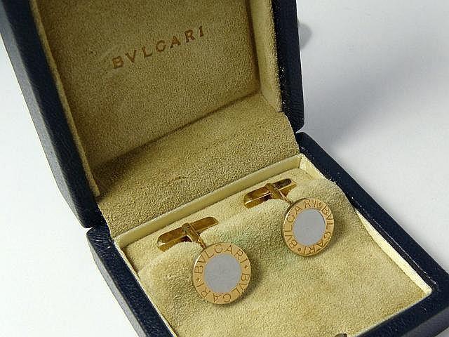 Paire de boutons de manchettes en or et acier, à décor de pastille gravée ''Bulgari''. Ils sont accompagnés d'un écrin siglé.. Poids brut: 10 g.